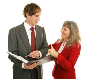 Female boss congratulating her young male employee, giving him a thumbs-up. Isolated on white.